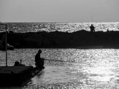 Angler am Hafen im Sonnenuntergang
